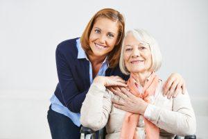 Lächelnde Frau bei der Altenpflege im Seniorenheim mit einer Seniorin